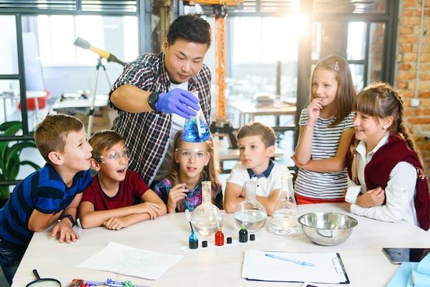 Gli alunni della scuola elementare guardano attentamente per il loro insegnante che mostra interessanti esperimenti chimici con liquidi colorati in scaglie di vetro.