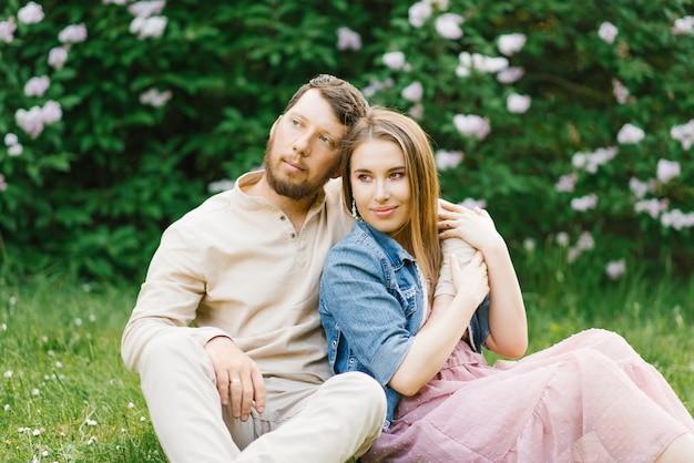 Gli amanti degli sposi in un appuntamento romantico siedono sull'erba in primavera