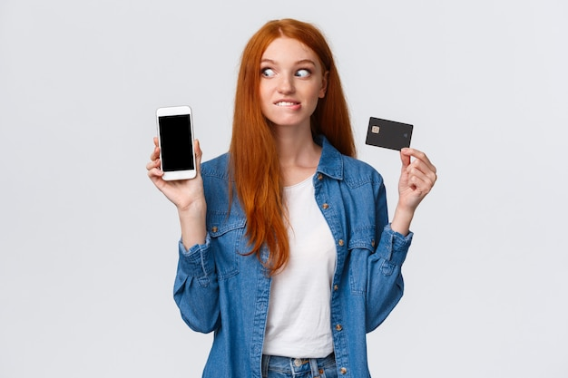 Gli amanti dello shopping non possono trattenersi dal voler comprare qualcosa online. la ragazza rossa ansiosa ed eccitata vede il negozio internet di prezzi allettanti, mostra lo smartphone mordere lo sguardo elettrizzato del labbro, tiene la carta di credito