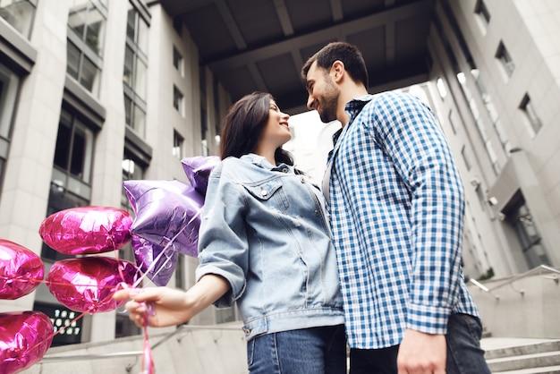 Gli amanti guardano negli occhi giovane coppia con palloncini.