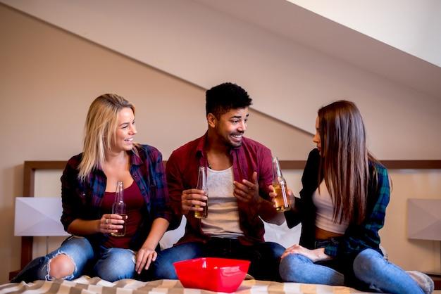 Gli amici allegri che raffreddano a casa fanno festa con la birra e le patatine fritte