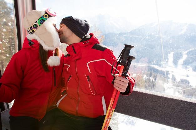 Gli amici allegri sull'ascensore di sci guidano su sulla montagna nevosa
