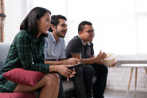 Gli amici asiatici stanno guardando la tv a casa. intrattengono