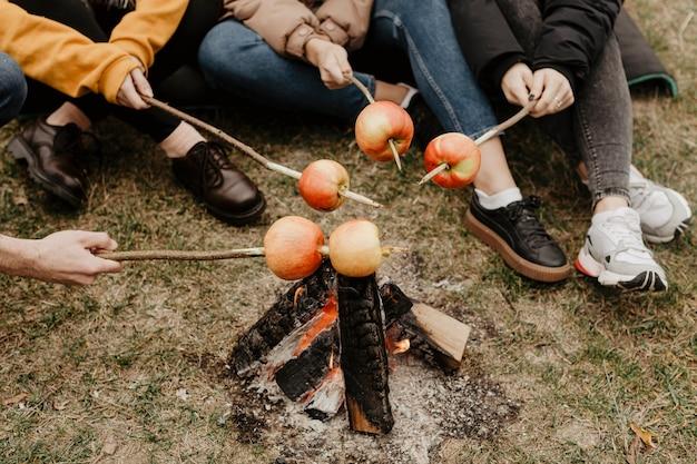 Gli amici che arrostiscono le mele all'aperto si chiudono su