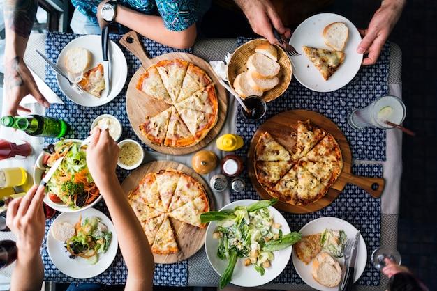 Gli amici che mangiano la pizza fanno festa insieme il concetto
