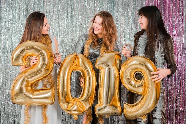 Gli amici che posano con gli aerostati dorati ad un partito degli amici del nuovo anno che posano con i palloni dorati ad un partito del nuovo anno