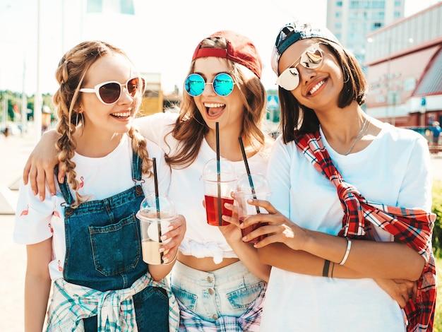 Gli amici che tengono e che bevono il frullato fresco del cocktail bevono in tazza di plastica con paglia