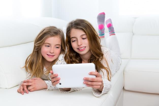 Gli amici dei bambini scherzano le ragazze che giocano insieme al pc della compressa