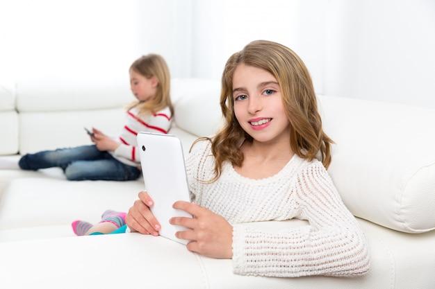 Gli amici della sorella scherzano le ragazze che giocano con il pc della compressa in sofà