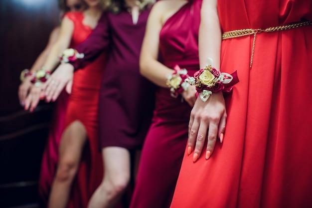 Gli amici della sposa si mostrano l'un l'altro manicure. abiti verdi. concetto di matrimonio, amicizia e moda. le amiche sfoggiano la manicure