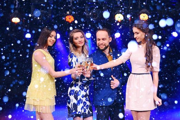 Gli amici festeggiano l'evento, ridono, ballano e bevono champagne