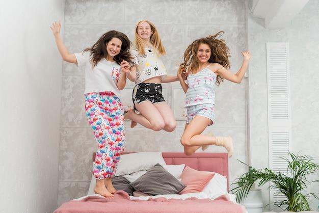 Gli amici in pigiama party saltano sul letto