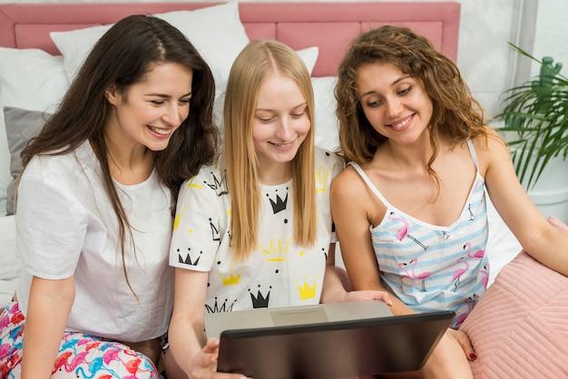 Gli amici in pigiama party utilizzando un computer portatile