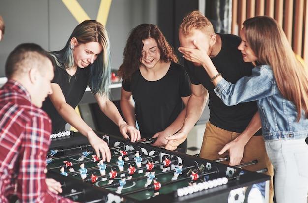 Gli amici insieme giocano a giochi da tavolo, calcio balilla