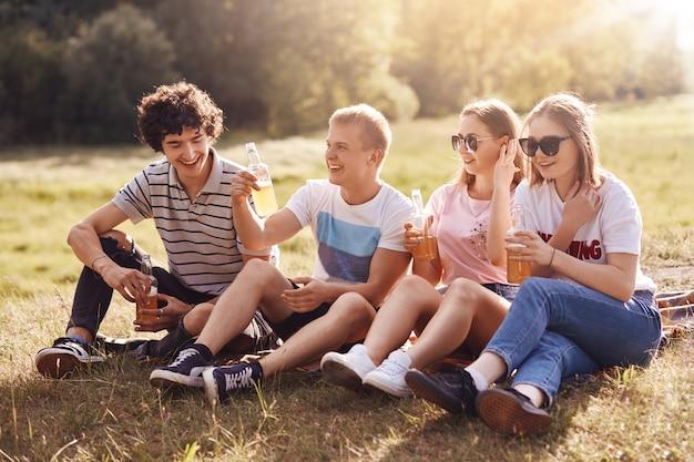 Gli amici positivi fanno picnic insieme, si ricreano all'aperto, si raccontano aneddoti, hanno espressioni gioiose, siedono sull'erba durante il periodo estivo, riposano bene e godono il clima estivo