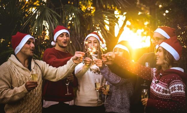 Gli amici raggruppano con i cappelli di santa che celebrano il natale con il brindisi del vino del champagne all'aperto