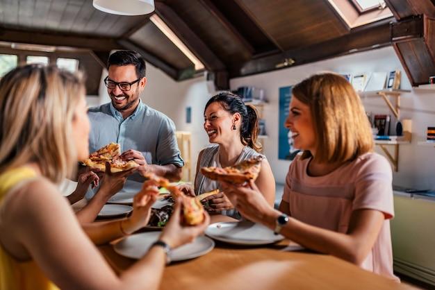 Gli amici si divertono a mangiare la pizza a casa. avvicinamento.
