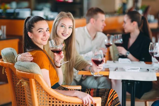 Gli amici si divertono bevendo vino, parlando e sorridendo nel ristorante.