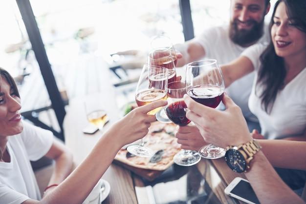 Gli amici si sono riuniti a tavola con cibo delizioso con bicchieri di vino rosso per festeggiare un'occasione speciale