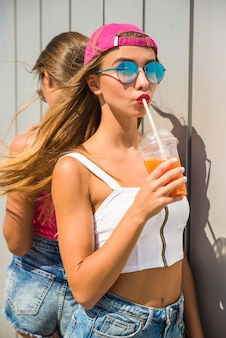 Gli amici sono in piedi l'un l'altro e bevono succo.