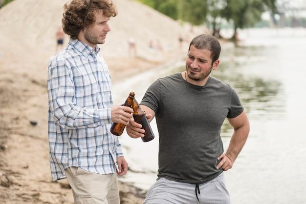 Gli amici tintinnano le bottiglie vicino al fiume