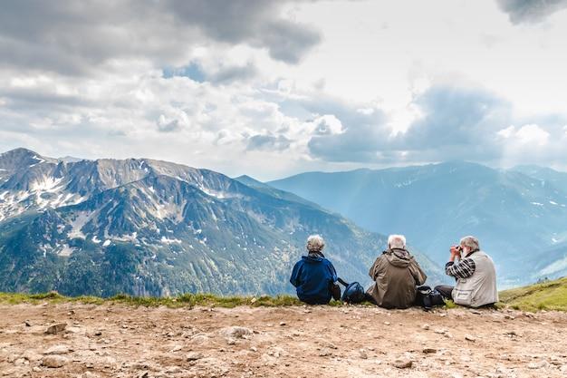 Gli anziani con gli zaini sono seduti per terra in alta montagna