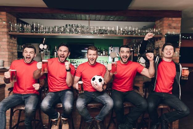 Gli appassionati di sport seduti in fila nel bar dello sport