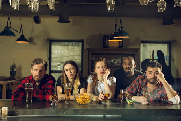 Gli appassionati di sport tifano al bar, pub e bevono birra mentre il campionato, la competizione sta andando