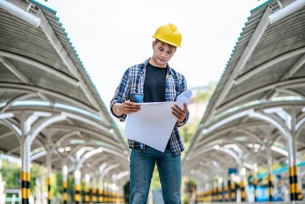Gli architetti tengono il piano di costruzione e controllano il lavoro.
