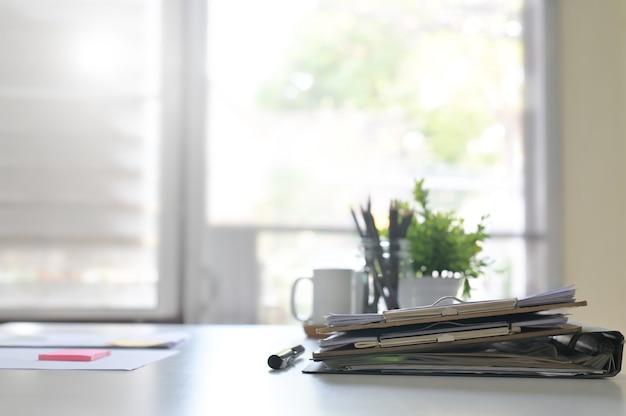 Gli archivi del documento cartaceo e l'attrezzatura aziendale della penna sulla tavola e sulla finestra dell'ufficio si accendono.