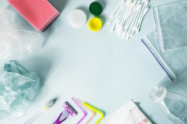 Gli articoli di plastica usa e getta di ogni giorno usano su sfondo blu