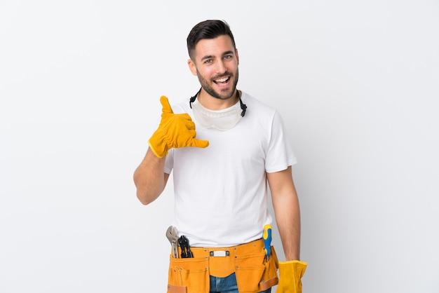 Gli artigiani o l'elettricista equipaggiano la parete bianca isolata che fa il gesto del telefono