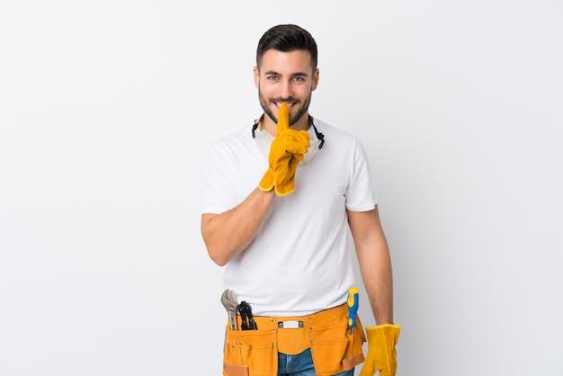 Gli artigiani o l'elettricista equipaggiano la parete bianca isolata che fa il gesto di silenzio