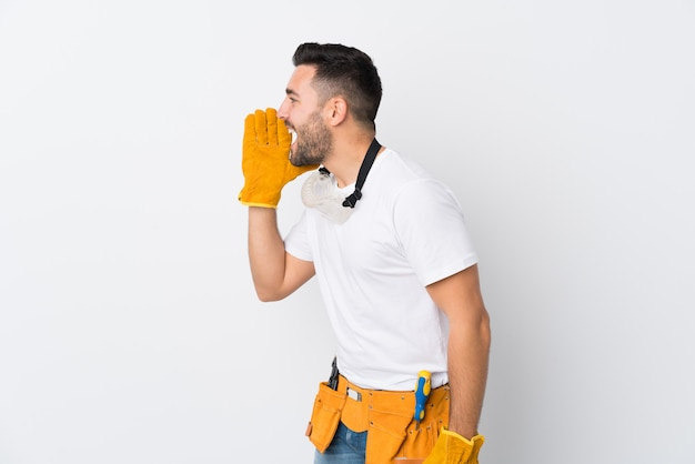 Gli artigiani o l'elettricista equipaggiano la parete bianca isolata che grida con la bocca spalancata