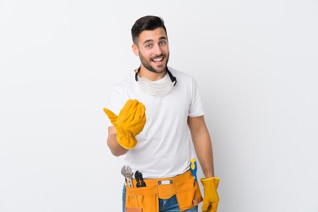 Gli artigiani o l'elettricista equipaggiano la parete bianca isolata che invita a venire