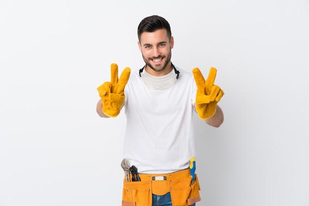 Gli artigiani o l'elettricista equipaggiano la parete bianca isolata che sorride e che mostra il segno di vittoria