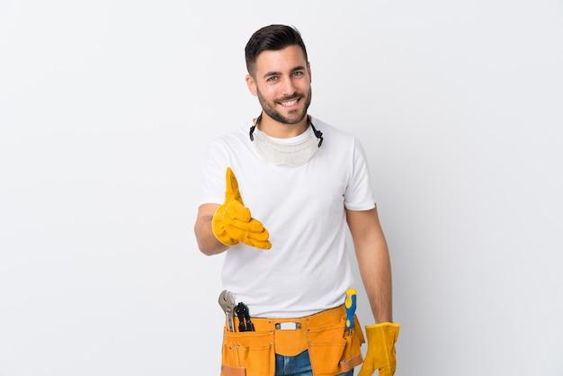 Gli artigiani o l'elettricista equipaggiano la stretta di mano isolata della parete bianca dopo il buon affare