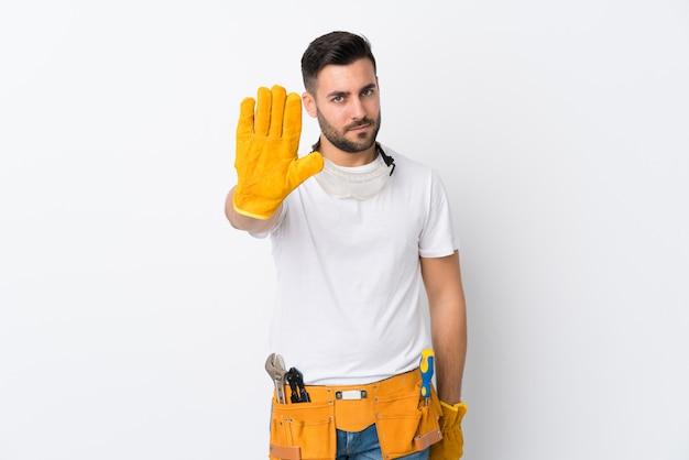 Gli artigiani o l'elettricista equipaggiano sopra la parete bianca isolata che fa il gesto di arresto con la sua mano
