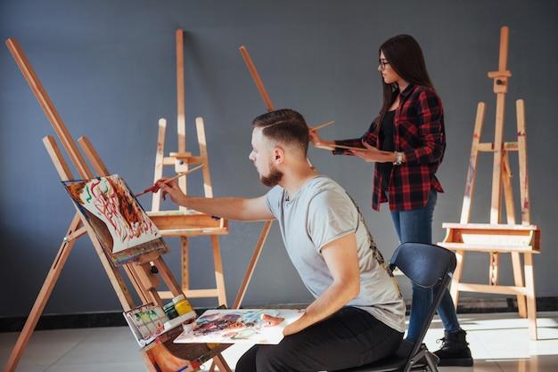 Gli artisti dipingono quadri in studio. gli artisti creativi hanno disegnato un quadro colorato dipinto su tela con colori ad olio