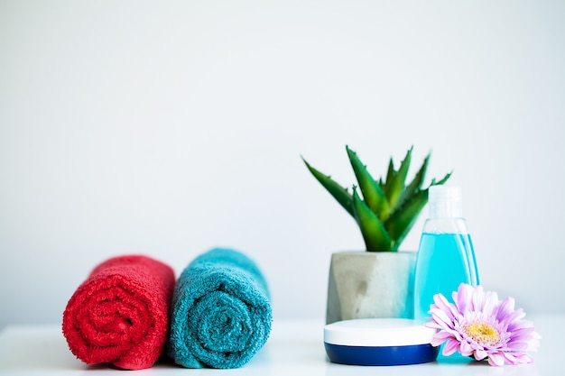 Gli asciugamani e la doccia gelificano sulla tavola bianca con lo spazio della copia sul fondo della stanza del bagno.