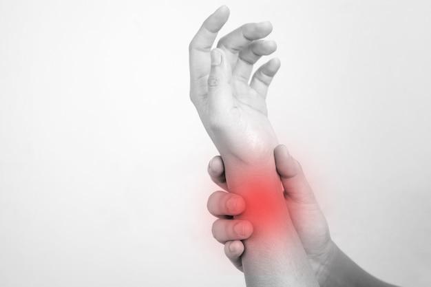 Gli asiatici massaggiano un polso doloroso su un bianco. concetto di dolore.