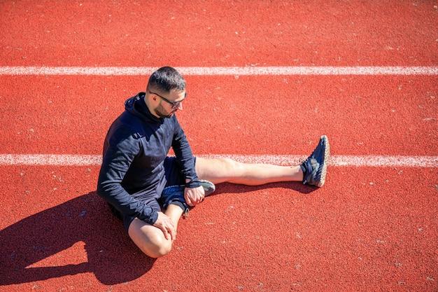 Gli atleti si allungano sulla pista bagnata rossa dell'atletica leggera