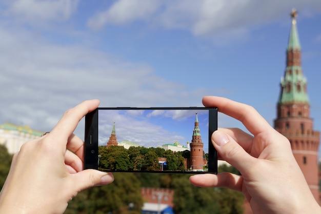 Gli edifici più famosi di mosca mostrano lo smartphone con le mani