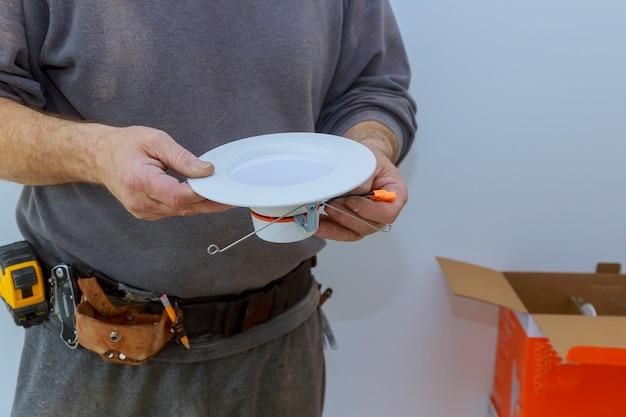Gli elettricisti a risparmio energetico stanno sostituendo la luce led a risparmio energetico dell'installazione