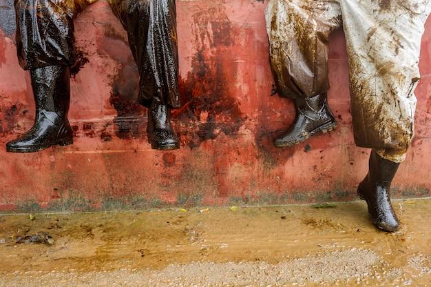 Gli equipaggi di pulizia riempiono sacchi con sabbia e detriti oliati dopo che una tubazione ha versato olio in un'area sensibile all'ambiente della spiaggia di ao prao, smet island, rayong, tailandia