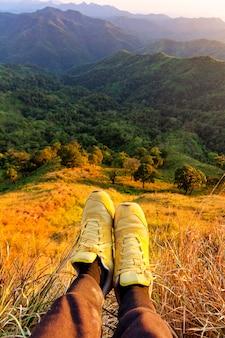 Gli escursionisti si sdraiano riposando e mostrano i piedi con una scarpa in cima alla montagna.