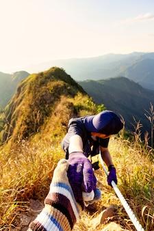 Gli escursionisti si tengono per mano aiutandosi a vicenda a malapena a scalare la montagna.