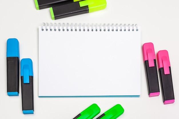 Gli evidenziatori e il foglio di carta per appunti in bianco disteso distesi su una scrivania