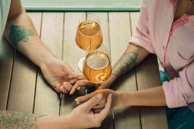 Gli ha detto di sì. primo piano del giovane che bacia la mano della moglie mentre fa la proposta di matrimonio all'aperto.