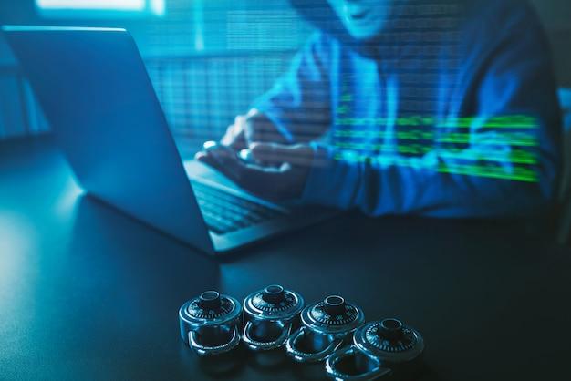 Gli hacker di persone asiatiche indossano una maschera usando un attacco informatico portatile.